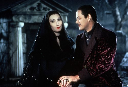 """Morticia: """"When we first met years ago, it was an evening much like this. Magic in the air. A boy."""" Gomez: """"A girl."""" Morticia: """"An open grave. It was my first funeral."""" Gomez: """"You were so beautiful. Pale and mysterious. No one even looked at the corpse."""""""
