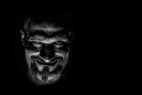 sinister looking bearded man in shadow