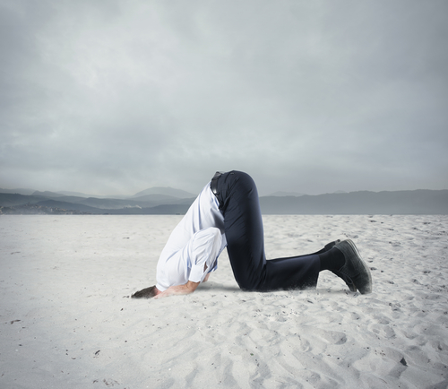 man in a business suit with his head in the sand