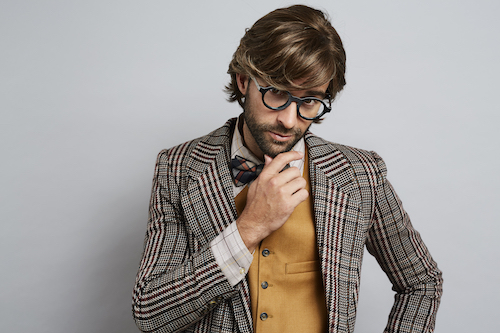 bearded young man in glasses, wearing a tweed jacket and tan waistcoat rubbing his chin
