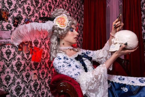 Contrapoints in 19th century French dress holding a skull and calipers