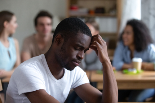 Lonely African American man, sitting alone in a cafe with group of friends in the background