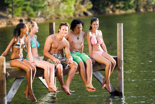 A group of young men and women sitting on a wooden pier over a lake
