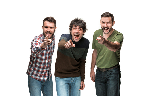 three men are laughing and pointing, looking and pointing at camera