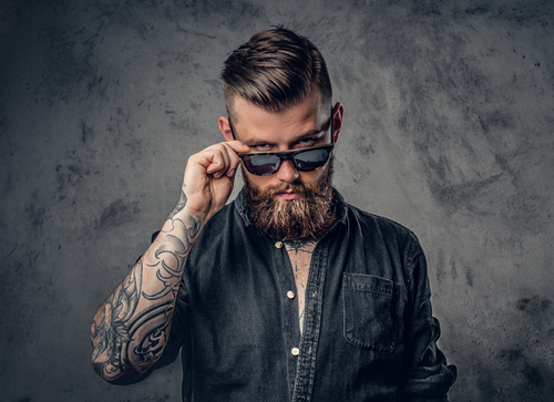 portrait of a bearded man with tattoos on his arms and neck dressed in a black shirt and sunglasses