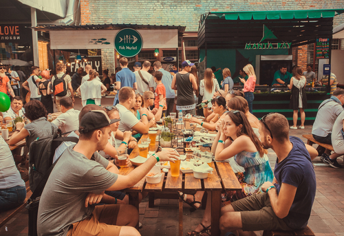 Friendly party with crowd of people eating at table during outdoor Street Food Festival