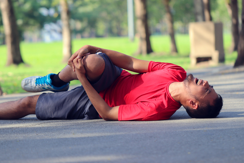 Runner clutching the knee, laying on the road in a public park