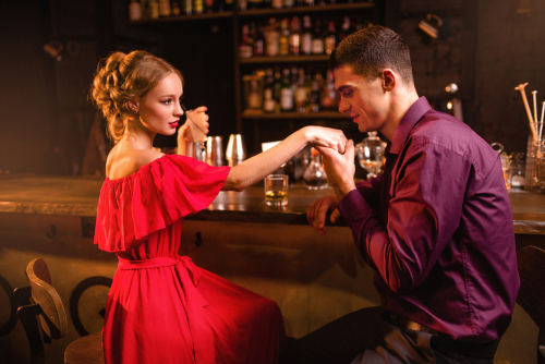 Man at bar about to kiss woman's hand