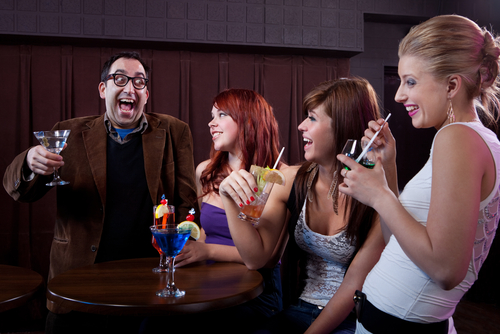 Nerdy looking man entertaining group of young women at the bar