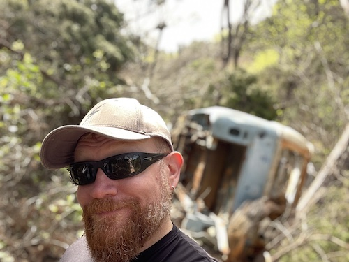Dr. NerdLove in sunglasses and a hat in front of an overturned old and rusty VW bus