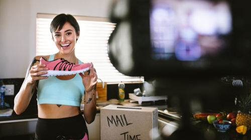 Smiling young woman vlogging about women's sports shoe