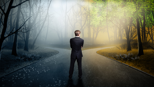 businessman standing at divergence of a road going in opposite directions