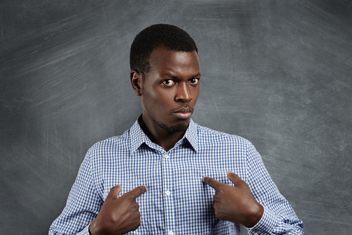 Headshot of young dark-skinned man pointing at himself, having perplexed and puzzled look as if saying: Who me?