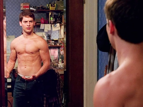 Tobey Maguire as Peter Parker, looking at his muscles in the mirror with his shirt off