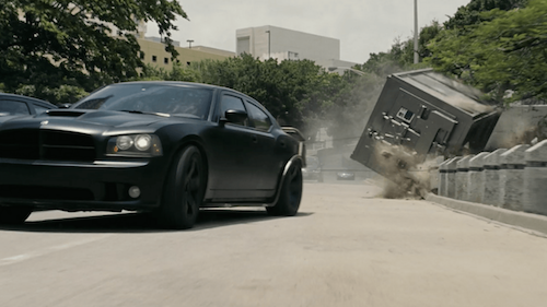 Screenshot from the movie Fast 5: Dom Toretto pulling a giant bank vault down a freeway in a Dodge Charger.