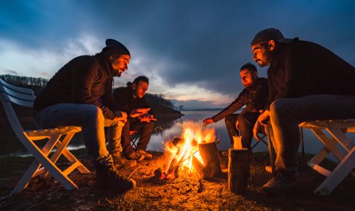 A group of four friends are sitting around the campfire and having fun on the lakeshore at dusk
