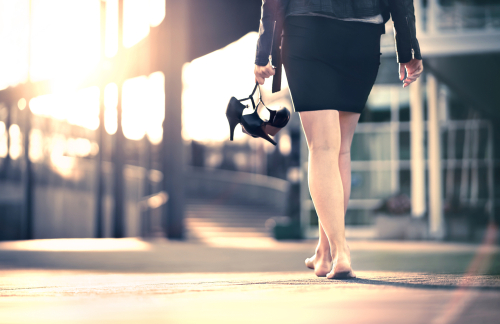 Woman holding high heels in hand and walking home from party barefoot