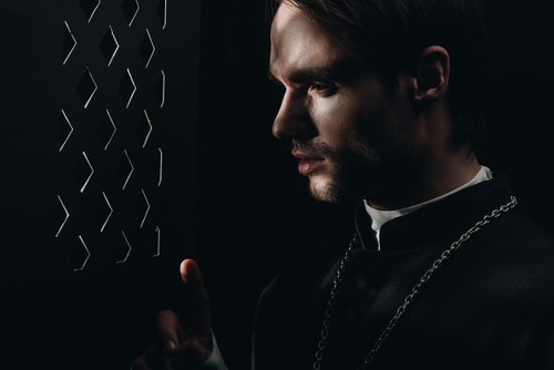 young tense catholic priest looking through confessional grille
