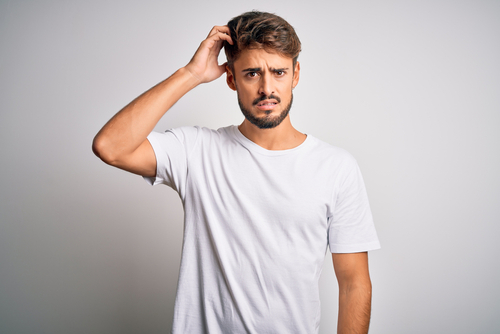 Young handsome man with beard wearing casual t-shirt standing over white background, scratching his head in confusion