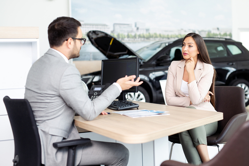 salesman negotiating price of car with female car buyer