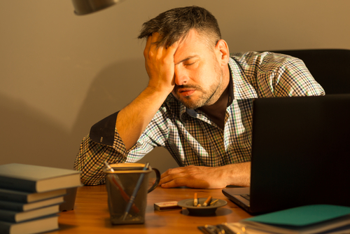 depressed man holding palm to forehead in front of laptop