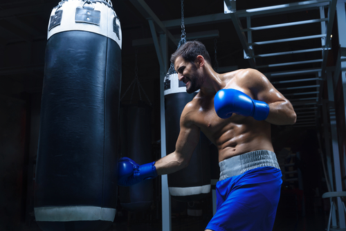 young male boxer beasting on the heavy bag in a dark gym