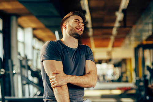 young man feeling the pain in hand at the gym