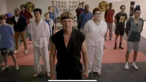 Johnny Lawrence and members of the Cobra Kai dojo facing the camera
