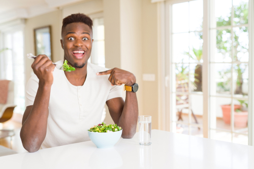 African american man eating fresh healthy salad with surprise face