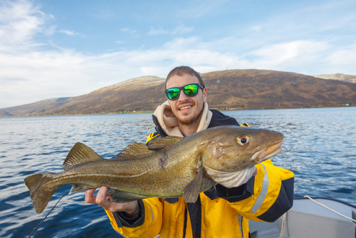 Happy fisherman with cod fish in hands