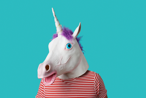 man wearing a unicorn mask and a red and white striped t-shirt on a blue background