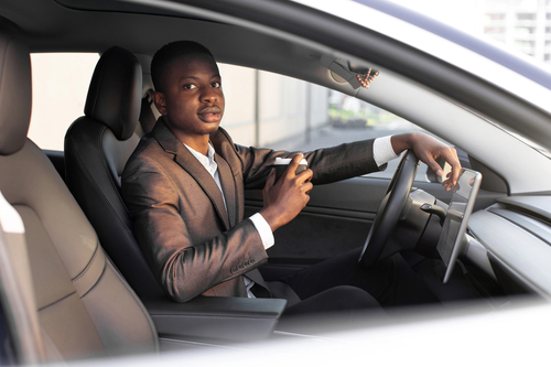 Handsome young dark skinned man in formal wear sitting in his modern electric car