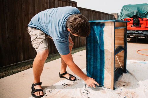 young man spray paints his wooden vinyl stereo stand DIY project