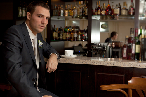 Worried man sitting at bar with tea cup