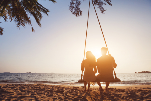 romantic couple in love sitting together on rope swing at sunset beach