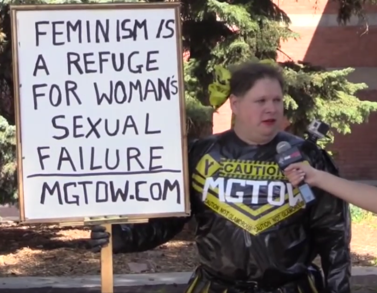 """Man in costume made of garbage bags with a logo on his chest that says MGTOW, holding a sign. Text reads """"Feminism is a refuge for womans sexual failure"""""""