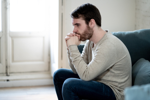 Unhappy depressed caucasian male sitting on a living room couch feeling lonely