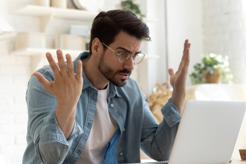 Angry frustrated annoyed young adult man consumer feel rage looking at computer notebook screen