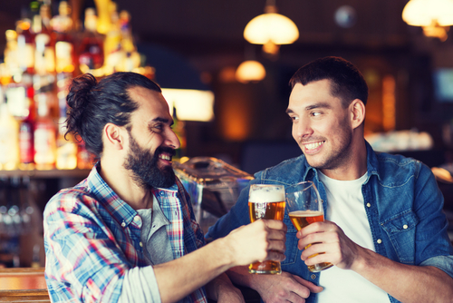happy male friends drinking beer and clinking glasses at bar