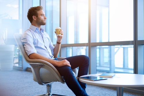 Man in chair holding a cup of takeway coffee in his hand and daydreaming while looking out of large windows