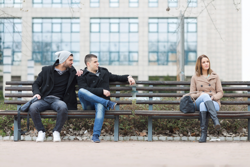 Two friends looking at a woman sitting on a park bench