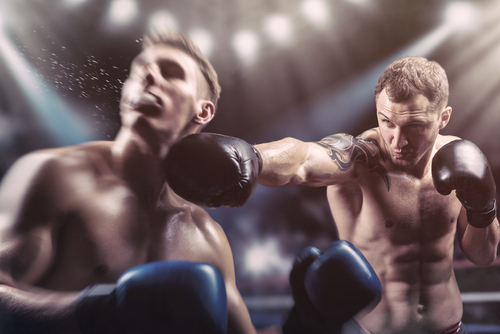 Two professional boxers fighting in the ring, one being punched in the face
