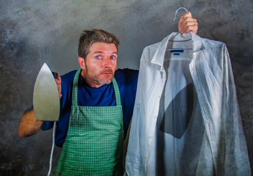 man in kitchen apron holding iron and burnt shirt with worried face expression