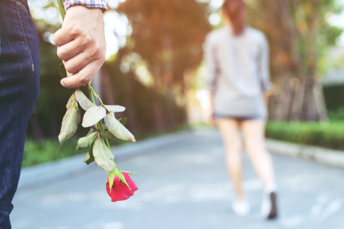 young man standing with a Red Rose on Hand with woman walking away in a park