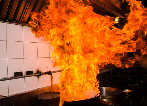 A kitchen fire over a stove, flames leaping out of a cast iron skillet