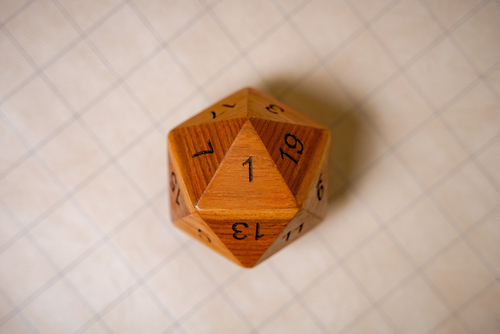 Close-up, big wooden 20 sided dice showing a bad roll of a natural 1