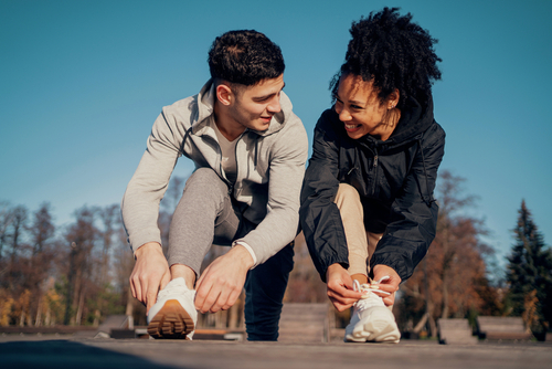 A man and a woman adjust their shoes on the street in a park, smiling at each other, a happy couple,