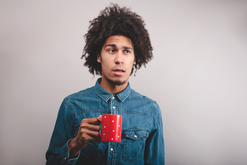 puzzled young man with cup of tea