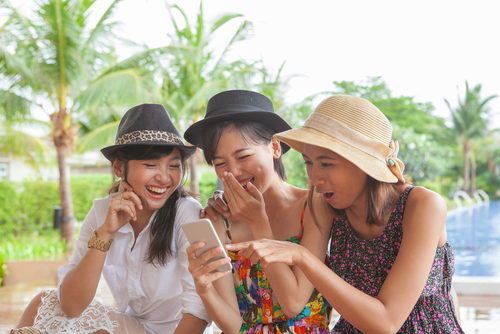 group of Thai woman friend looking to smart phone and laughing