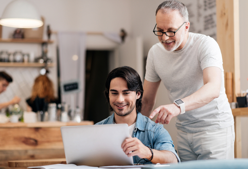 Positive young man and his smiling father using laptop being in a cafe